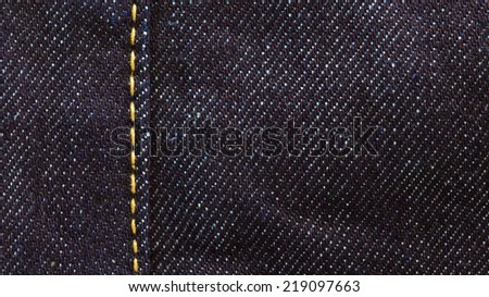 close up shot of raw denim dark wash indigo blue jeans texture background - stock photo