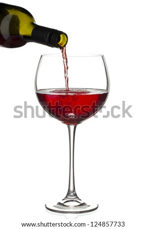 Close-up shot of red wine bottle pouring wine in wine glass against white background. - stock photo