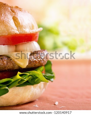 Close-up shot of right side of a cheeseburger on table - stock photo