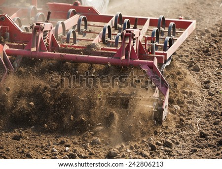 Close up shot of seedbed cultivator machine at work - stock photo