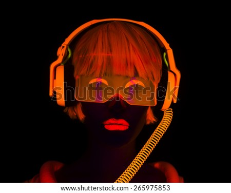 close up shot of sexy female disco dancer posing in UV costume with headphones