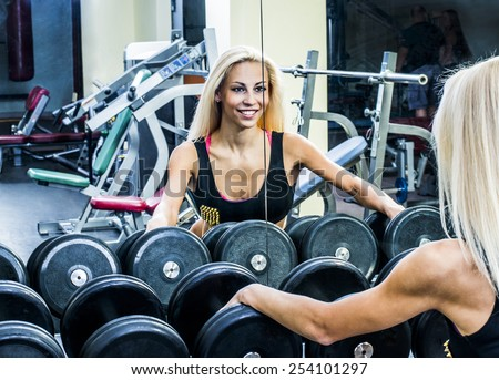 close-up shot of the torso of a female dressed in fitness wear, holding a hand weight,facing the camera. Woman look at your self reflection mirror image Arm keep black metal dumbbell - stock photo