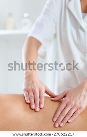 Close up shot of therapist hand doing massage on spa treatment - stock photo