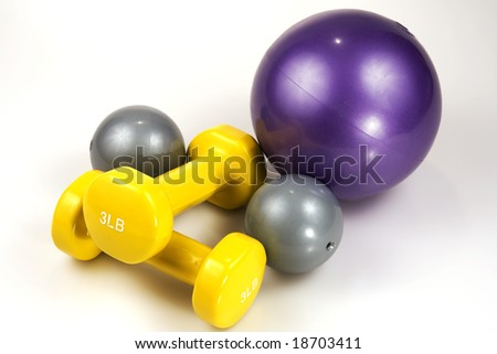 Close up shot of three medicine balls and two lifting weights - stock photo