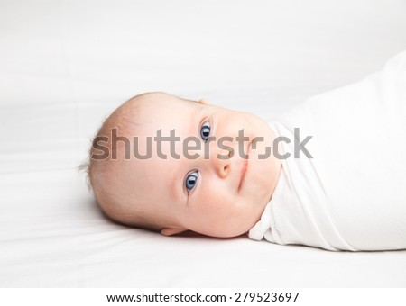 Close-up shot of three month baby girl swaddled in white blanket laying on a bed. Swaddling is a practice of wrapping infants in cloths in order to prevent limb movement - stock photo