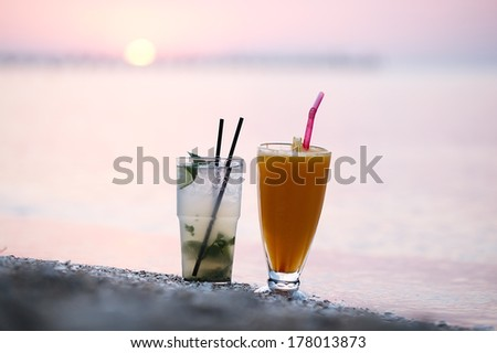 Close up shot of two fruity alcoholic cocktails mojito and orange juice standing side by side in their tall glasses in the sand on a tropical beach at sunset against a colourful pink sky - stock photo