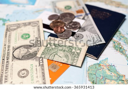 Close up shot of US currency with passport and credit cards, with a map for a background. Business travel and tourism concept - stock photo