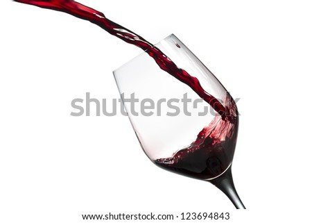 Close-up shot of wine being poured in wine glass against white background. - stock photo