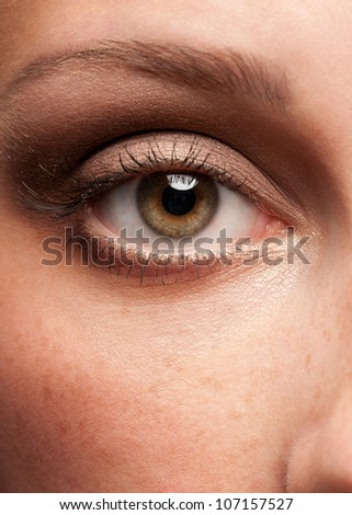 Close-up shot of woman eye with beautiful makeup looking at camera - stock photo