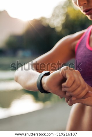 Close up shot of young woman jogger ready to run set and looking at sports smartwatch. Fitness female checking her performance. - stock photo