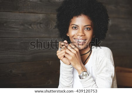 Close up shot ofattractive happy cheerful dark-skinned young woman looking and smiling at the camera, showing white teeth with braces, holding hands at her face. Human face expressions and emotions - stock photo
