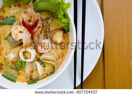 Close up shot Tom yam kung Soup thai cuisine and dry chilly on colorful soup and spicy on yellow wooden background - stock photo