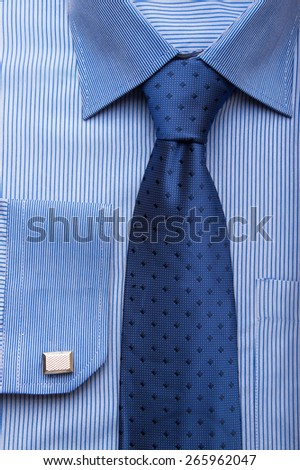 Close up shots of blue striped man's shirt with blue dotted tie and cuff links - stock photo