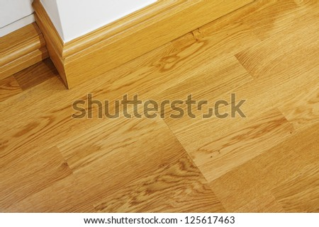 Close up showing some laminate flooring and mdf imitation wood skirting boards in newly constructed house - stock photo