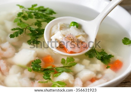 Close up shrimp and fish, selective focus on single piece in spoon, soup in bowl.  - stock photo
