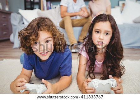 Close-up siblings with remote playing video games on carpet at home - stock photo