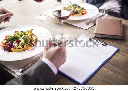 Close-up. Side view. Businessmen during a business lunch in restaurant. - stock photo