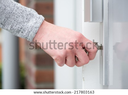 Close up side view female hand inserting key in door - stock photo
