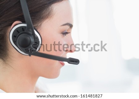 Close up side view of a businesswoman wearing headset in office - stock photo