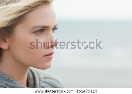 Close up side view of a serious cute young woman on the beach - stock photo