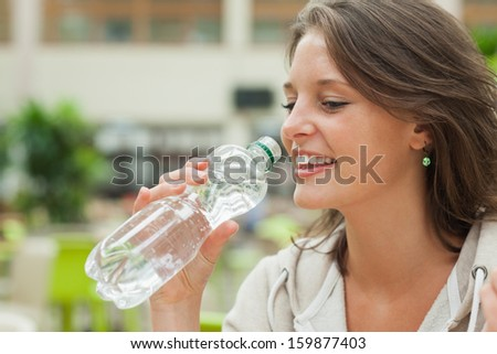 Close-up side view of a young woman drinking water against blurred background - stock photo