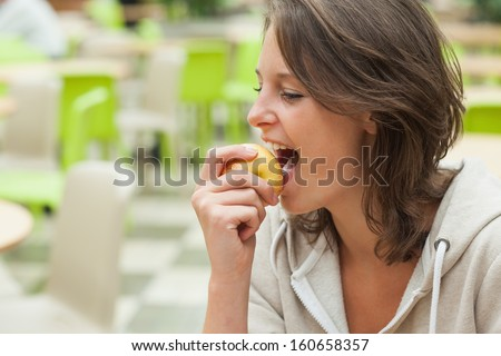 Close-up side view of a young woman eating apple in the cafeteria - stock photo