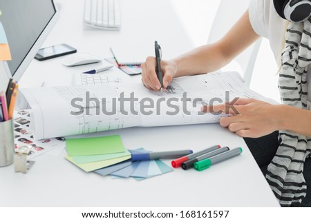 Close-up side view of an artist drawing something on paper with pen at the office - stock photo