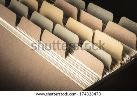 Close up side view of blank card index at slight angle.  Low saturation hues and vignette applied to give a vintage feel.  Left blank to provide copy space. - stock photo