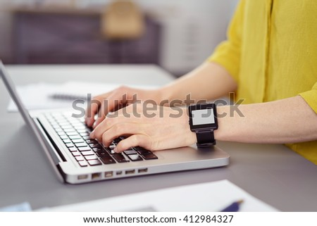 Close up side view on hands of person typing on laptop while wearing a smart watch on her wrist in office - stock photo