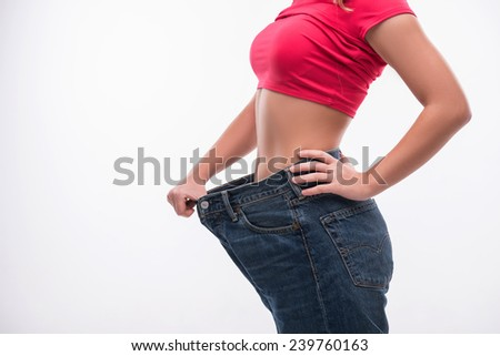 Close-up side view portrait of slim waist of young woman in big jeans showing successful weight loss, isolated on white background - stock photo