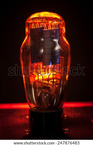 Close up silhouette of electronic vacuum tube, with incandescenden filament in a black background - stock photo