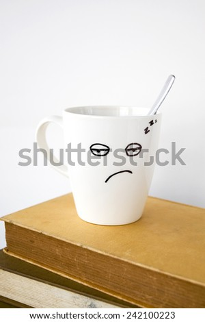 close up sleepy face on coffee cup put on books - stock photo