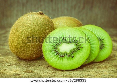 Close up slice of fresh kiwi fruit on old wood background, shallow depth of field (DOF) kiwi fruit in focus. Kiwi fruit is sweet and sour taste, nutritive value and high-fiber. Vintage picture style. - stock photo