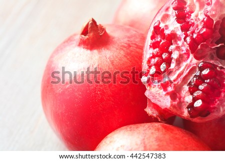 Close up sliced and whole pomegranate on a table - stock photo