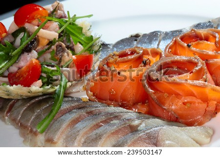 close-up sliced fish of different varieties decorated with greens and tomatoes on white dish - stock photo