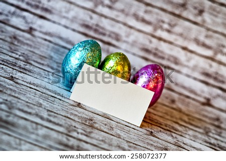 Close up Small Blank Rectangular Greeting Card with Shiny Colored Easter Chocolate Eggs on a Rustic Table in a Diagonal Shot. - stock photo