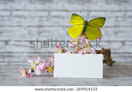 Close up Small Empty Greeting Card In Front of Orchid Flowers with Yellow Green Butterfly on Top of the Table with Abstract Background. - stock photo