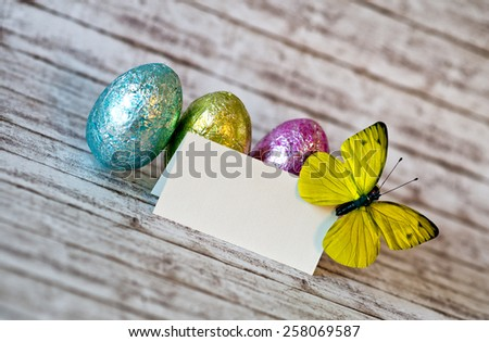 Close up Small Empty White Greeting Card with Yellow Green Butterfly on the Upper Corner and Colored Glossy Easter Eggs on Top of a Wooden Table in a Diagonal Shot. - stock photo