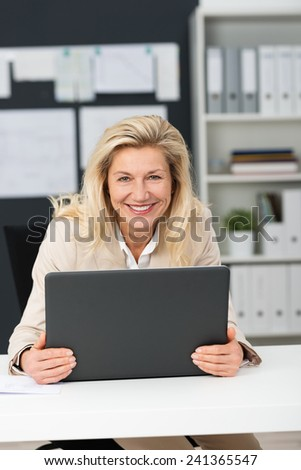 Close up Smiling Adult Corporate Woman Holding Gray Laptop on White Desk While Looking at the Camera. - stock photo