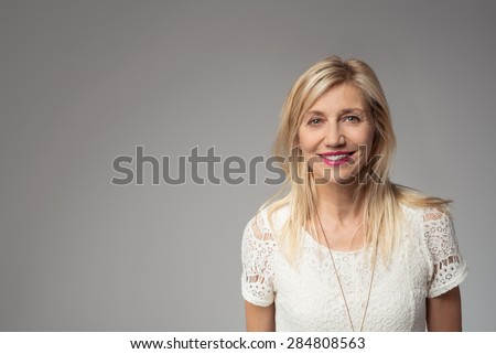Close up Smiling Blond Adult Woman Looking at the Camera Against Gray Background with Copy Space for Texts - stock photo