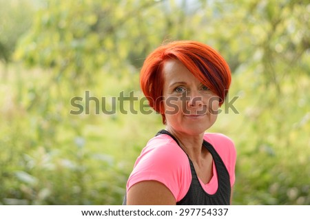 Close up Smiling Middle Aged Redhead Woman Looking at the Camera Against Blurry Green Plants. - stock photo