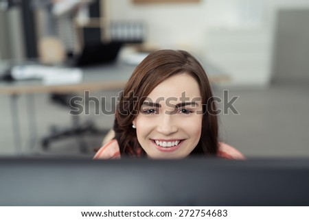Close up Smiling Pretty Girl Peeking Over Computer Monitor Inside the Office While Looking at the Camera. - stock photo