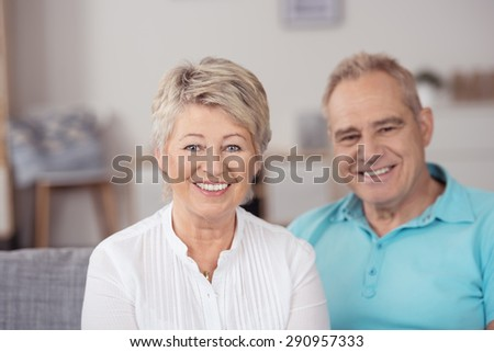 Close up Smiling Pretty Senior Blond Wife Sitting on the Couch Beside her Husband, Looking at the Camera. - stock photo