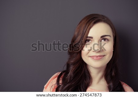 Close up Smiling Thoughtful Cute Girl Looking Up on a Gray Wall Background with Copy Space - stock photo