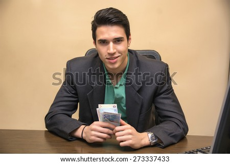 Close up Smiling Young Businessman, Sitting at his Worktable, Counting Cash on Hand - stock photo