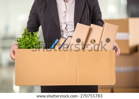 Close-up. Smiling young businesswoman holding cardboard box with her things. - stock photo