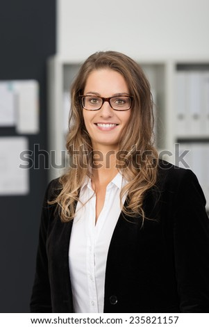 Close up Smiling Young Businesswoman, in Black Coat and Eyeglasses, with Long Blond Hair, Looking at the Camera Inside the Office. - stock photo