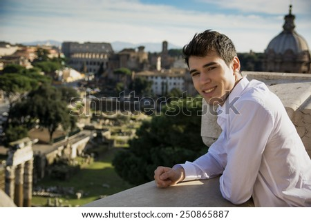 Close up Smiling Young Man at the Terrace Looking at the Outdoor View in Rome, Italy - stock photo