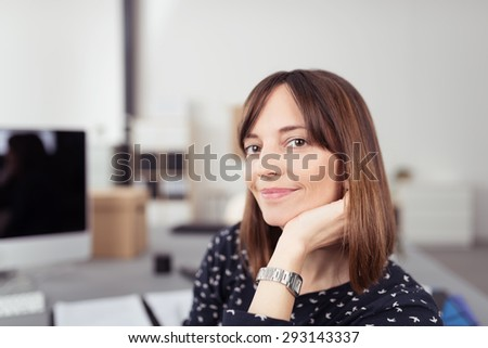 Close up Smiling Young Office Woman, Sitting at her Desk, Leaning on her Hand While Looking at the Camera. - stock photo