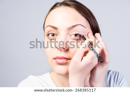 Close up Smiling Young Woman Applying Eyeliner Makeup to Left Eye While Looking at the Camera on a Gray Background. - stock photo